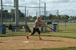 Girl hitting softball on field