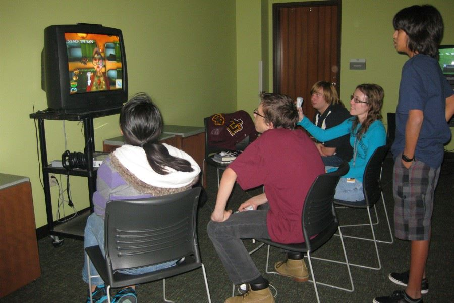 Teens sitting down at Library playing video games